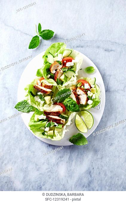 Lettuce boat filled with chicken breast, cucumber, avocado, feta and herbs
