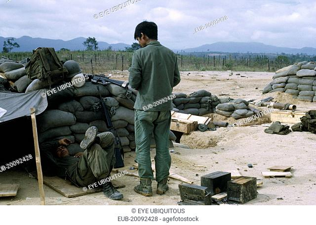 Vietnam War. Siege of Kontum. Montagnard soldiers in camp within defensive perimeter, with sand bags and makeshift shelters