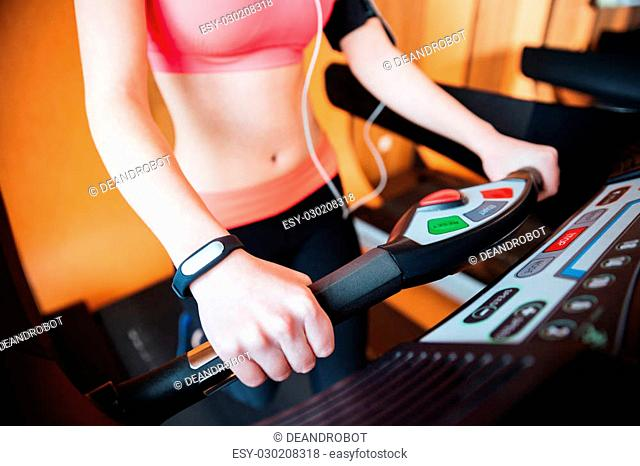 Closeup of treadmill used by young sportswoman with fitness tracker on her hand