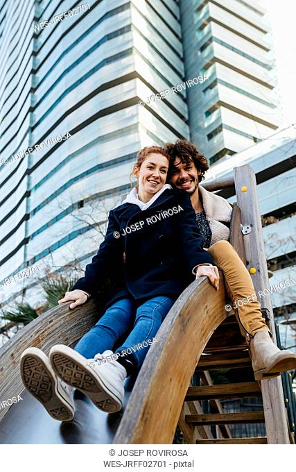 Portrait of happy couple on a slide at a playground in the city