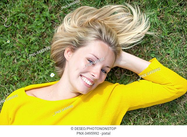 Portrait of a pretty blond woman lying down in the park smiling at camera