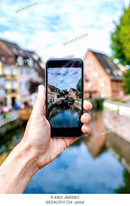 France, Colmar, close-up of a hand of a man taking a picture with his smartphone