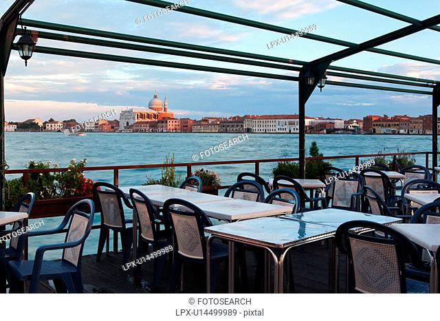 View of Canale della Giudecca, looking towards church of Il Redentore, at sunset, with empty outdoor restaurant in foreground, autumn in Venice, Northern Italy