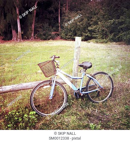 A bicycle sitting beside a barb wire fence in the countryside