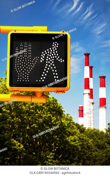 Crosswalk signal with smoke stacks in the background, New York City, New York State, USA