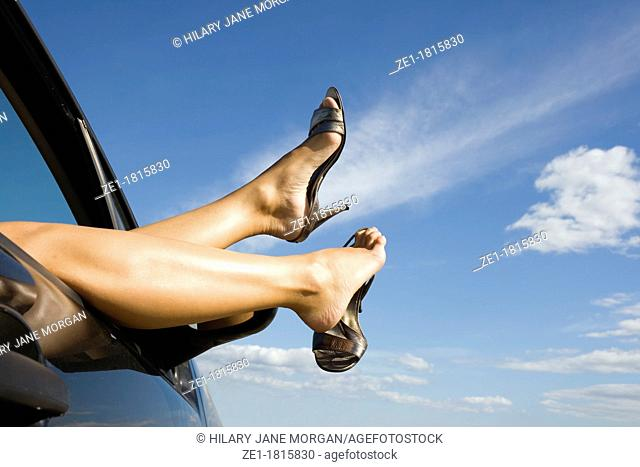 Woman's legs and feet wearing silver high heeled shoes sticking out of car window