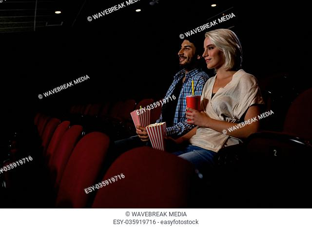 Couple having popcorn while watching movie in theatre