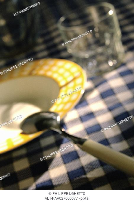 Bowl, spoon and glass on checked tablecloth, close-up, blurred