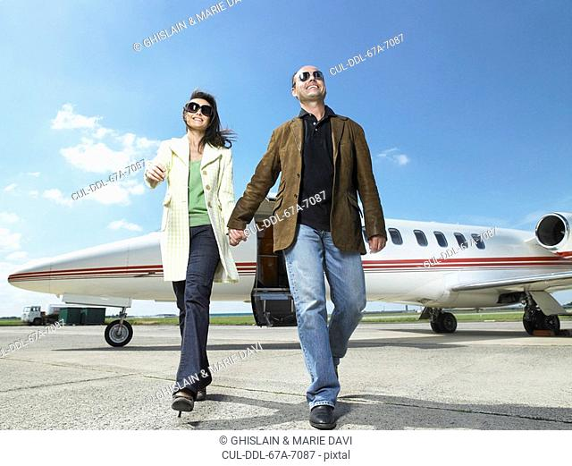 Happy couple walking away from private jet