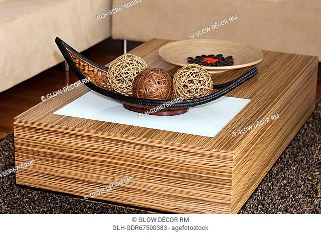 Decorative wicker balls and pebbles on a wooden plate on a table