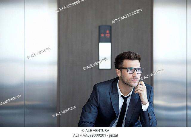 Businessman sitting in lobby, looking away in thought