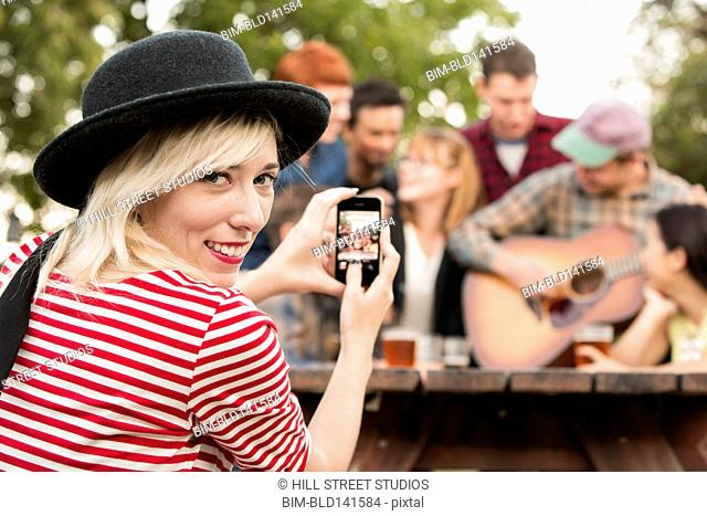 Woman taking cell phone picture of friends at party