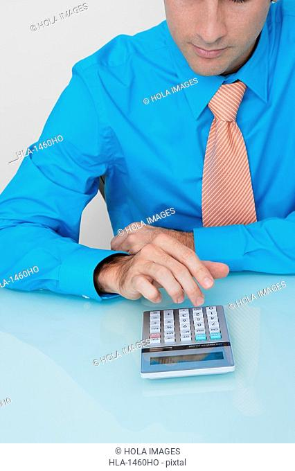 Businessman using a calculator in an office