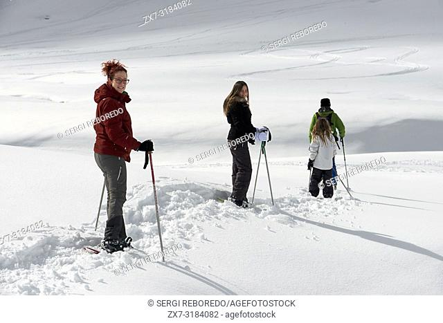 Baqueira Beret, Ski resort, Pyrenees, Aran Valley, Lleida, Catalonia, Spain. Line of people walking with snow rackets towards the summit of a snowy hill