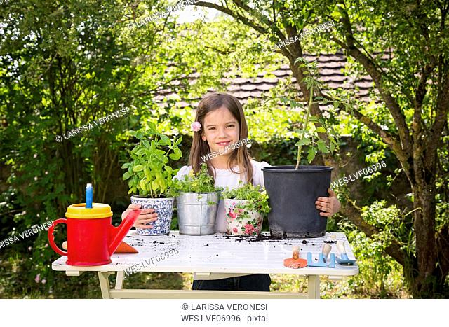 Portrait of proud little girl with potted spice plants on table in the garden