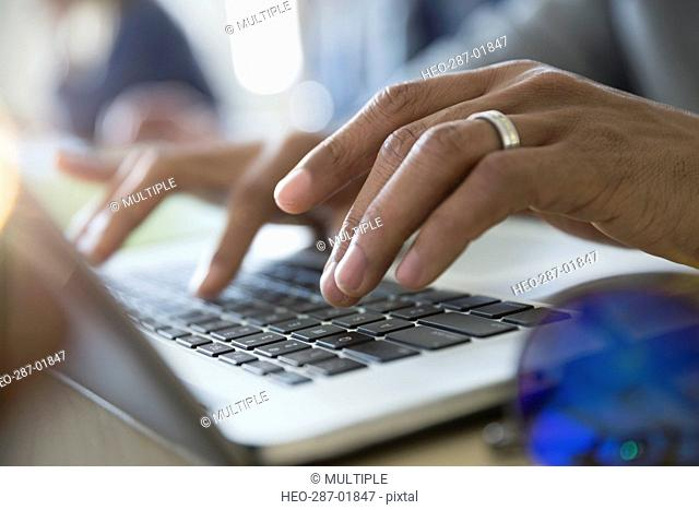 Close up adult education student typing on laptop