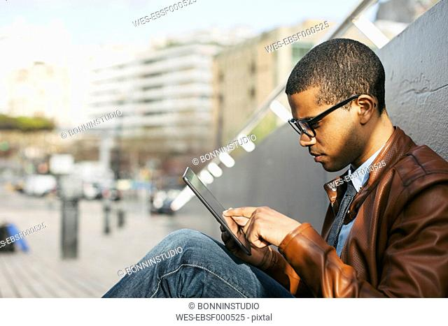 Businessman sitting outside using mini tablet