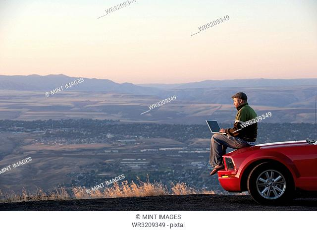 Caucasian male sitting on the hood of his car working on a lap top computer at a rest stop near Lewiston, Idaho USA