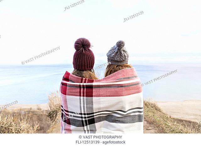 Two friends wrapped in a blanket standing on bluffs looking out over Lake Ontario; Scarborough, Ontario, Canada