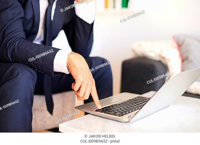 Mid section of businessman sitting on armchair using laptop