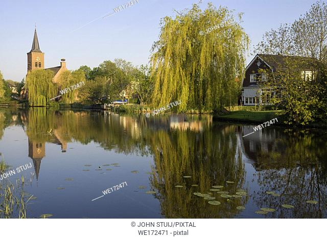 View over th river Graafstroom to the church of the small village Bleskensgraaf in the Dutch region Alblasserwaard