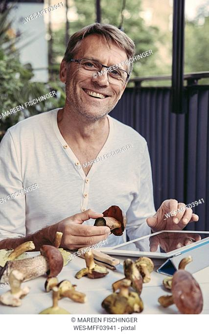 Portrait of laughing man with tablet holding scarletina bolete