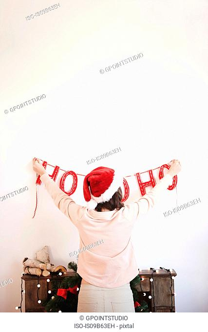 Rear view of young woman putting up christmas decorations on wall