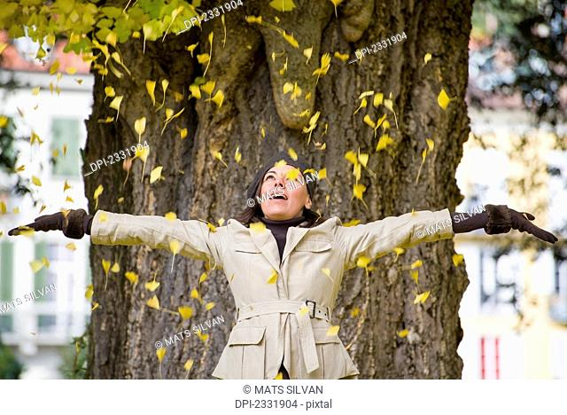 A woman stands in front of a tree with arms outstretched as yellow leaves shower down on her;Locarno ticino switzerland