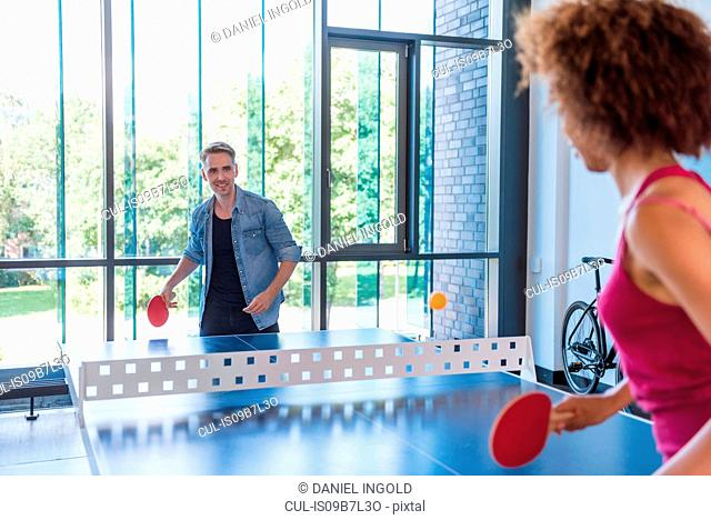 Couple practicing table tennis in apartment