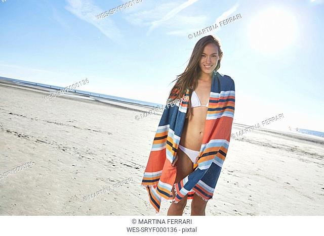 Smiling young woman in bikini with blanket on the beach