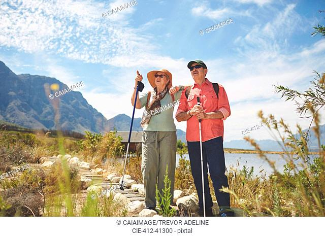 Active senior couple hiking with hiking poles at sunny summer lakeside