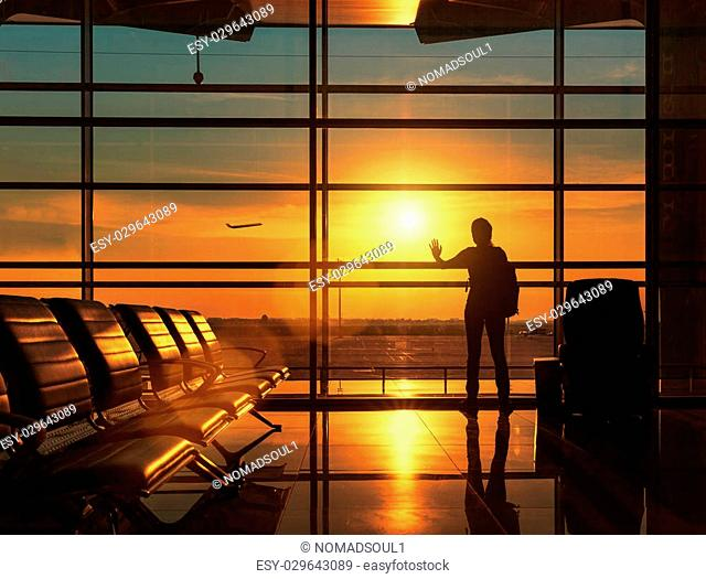 Silhouette of traveling woman waiting for the flight in airport at sunset