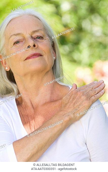 Elderly lady clapping herself on the shoulder