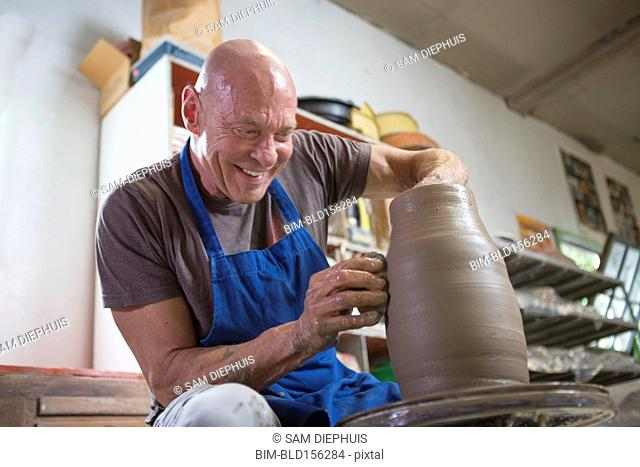 Older Caucasian man forming pottery on wheel in ceramics studio