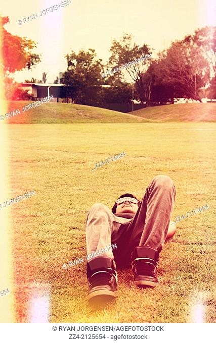 Faded old style photograph of a person lying down on back when in a state of relax at the local park. Spring break