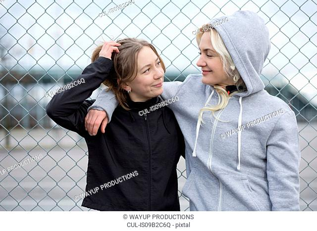 Two happy female runner friends by wire fence