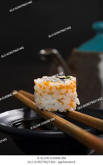 Close-up of a maki sushi with chopsticks on a bowl