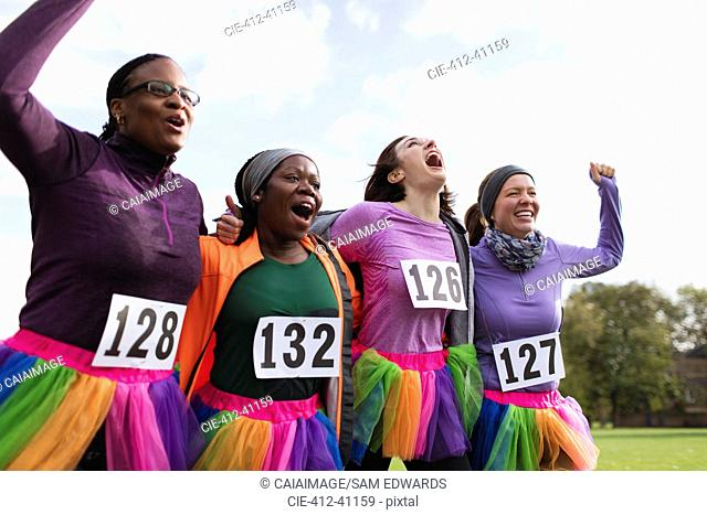 Enthusiastic female runner friends in tutus cheering at charity run