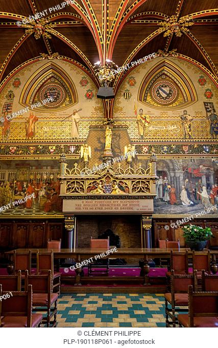 Interior of Bruges' city hall showing the Gothic hall with monumental mantelpiece, polychrome vault and 19th century murals, West Flanders, Belgium