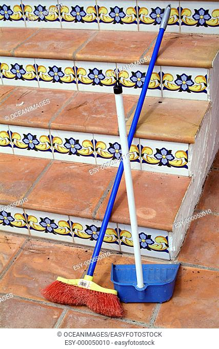 Broom and dust pan by stairs