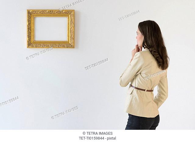 Woman looking at blank picture in art gallery