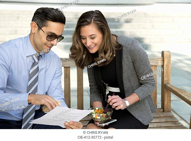 Corporate businessman and businesswoman eating lunch and reviewing paperwork on bench