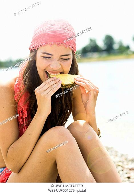 Portrait of young woman eating slice of pineapple on the beach