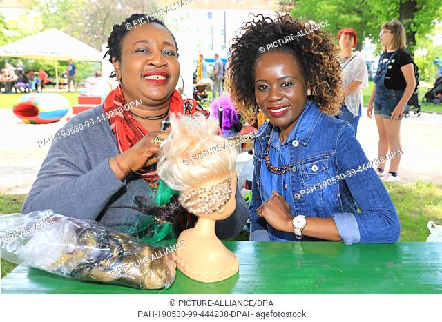 30 May 2019, Saxony-Anhalt, Magdeburg: Akue from Togo (l) and Geradine Muponda from Simbawe offer to weave rasta plaits at the festival of encounter