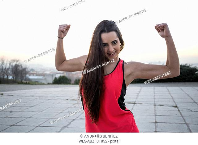 Smiling female athlete flexing her muscles