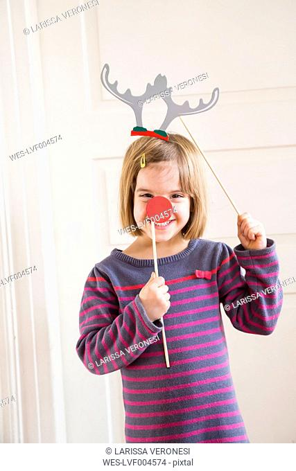 Portrait of little girl with toy antler and red nose