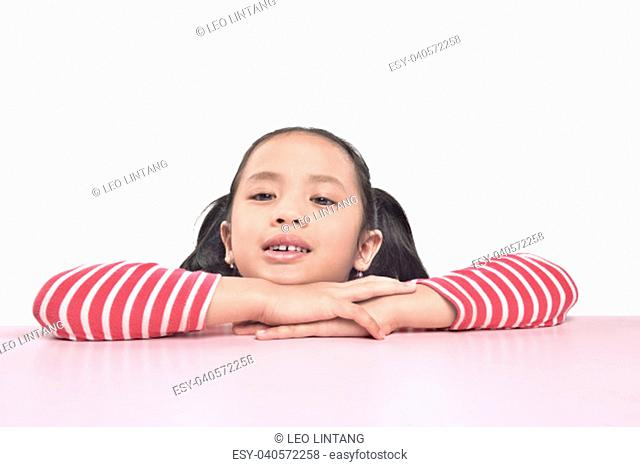 Portrait of asian little girl lean on the table posing isolated over white background