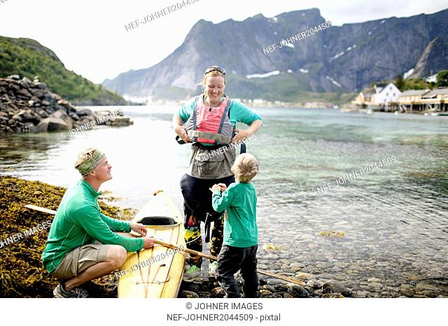 Parents with son near kayak
