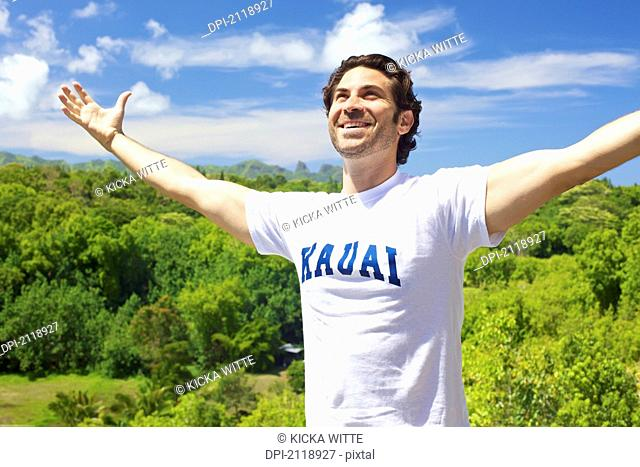 A Smiling Man Stands With Arms Raised And Lush Vegetation In The Background;Wailua Kauai Hawaii United States Of America