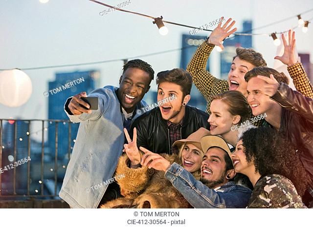 Enthusiastic young adult friends cheering and taking selfie at rooftop party